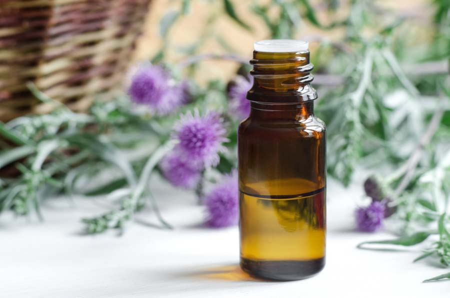 essential oil bottle with basket and thistle