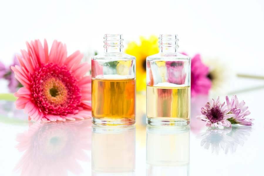 essential oils bottles bright flowers white background