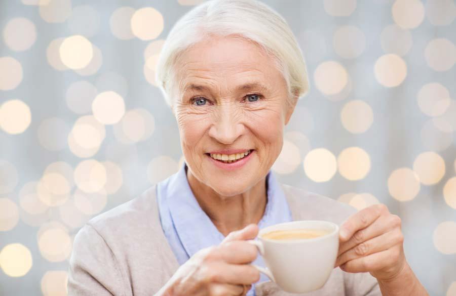 older woman smiling enjoying coffee