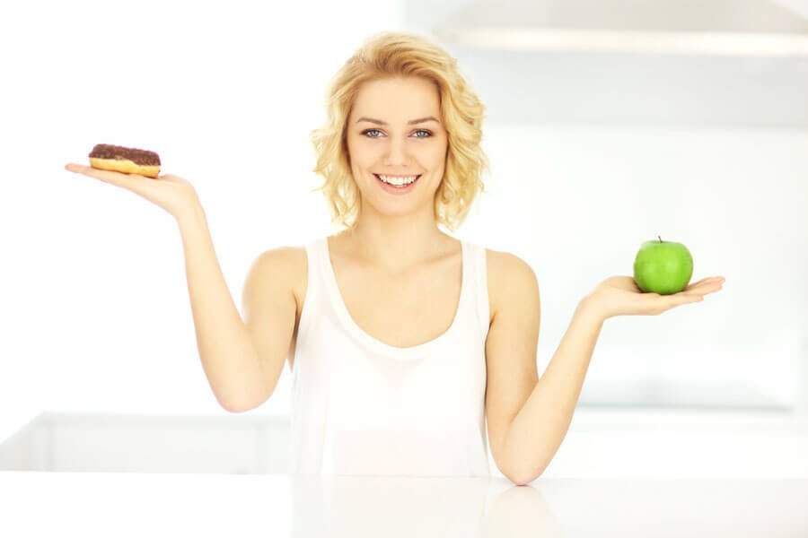 woman holding up unhealthy and healthy food