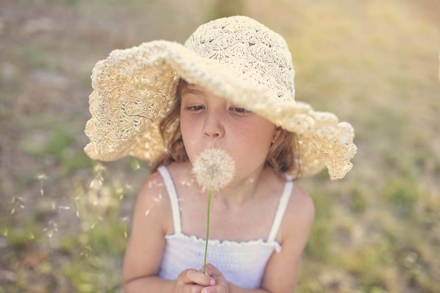 young girl blowing seeds from flower