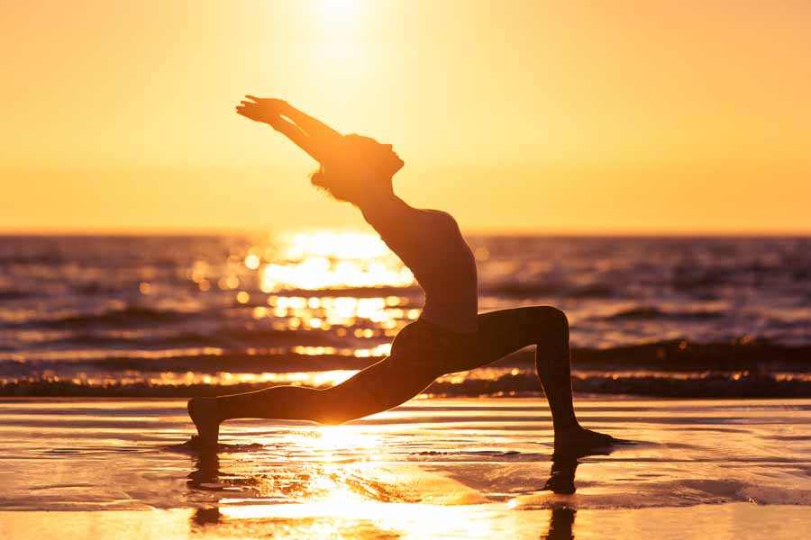 young woman doing yoga on beach with waves